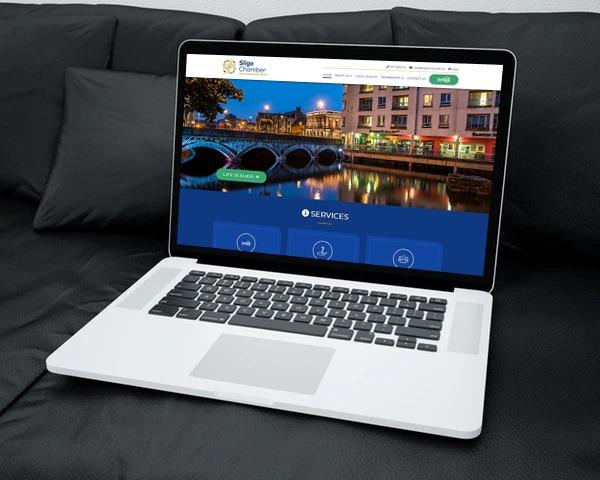 Laptop on sofa showing Sligo Chamber of Commerce website open
